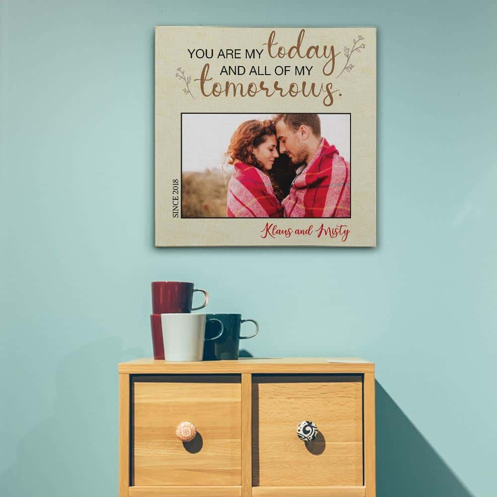 "A custom photo canvas with the quote ""You Are My Today And All Of My Tomorrows"" hung above a bed"