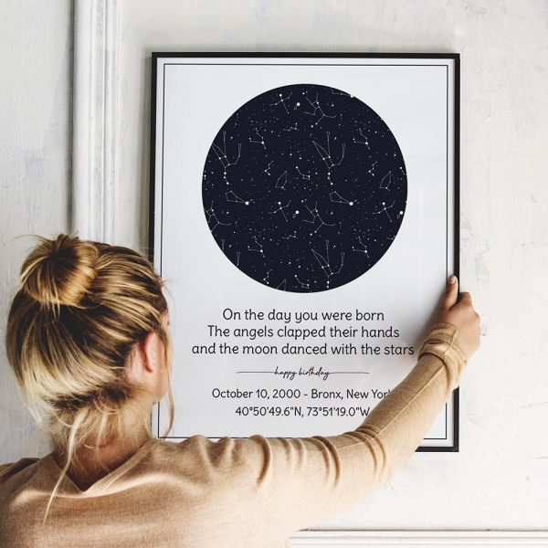a woman hanging a custom star map print on the wall